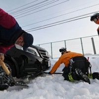 雪の深みにはまった乗用車を出そうとする消防隊員ら=福井市で2021年1月11日午後3時24分、山田尚弘撮影