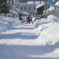 道路の雪かきに追われる住民たち=福井市で2021年1月11日午後1時47分、山田尚弘撮影