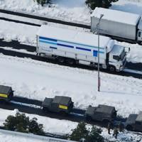 大雪で渋滞した国道8号。手前は自衛隊員=福井県坂井市で2021年1月11日午後0時1分、本社ヘリから木葉健二撮影