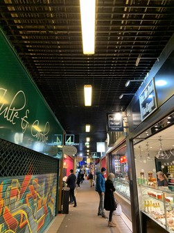 イートインスペースもあるポールボーキューズ市場の通路。年末年始はフォアグラ、カキ、トリュフなどの食材店が出店する。営業できない一部のレストランでは予約テークアウトサービスで対応中=筆者撮影