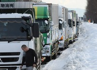 Trucks are seen stranded in the snow on National Route 8 in the central Japan city of Fukui on Jan. 11, 2021. (Mainichi/Naohiro Yamada)