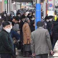 博多駅前でバスを待つ人たち=福岡市博多区で2021年1月13日午前8時5分、津村豊和撮影