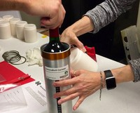 In this Nov. 2, 2019 photo provided by Space Cargo Unlimited, researchers from the company prepare bottles of French red wine to be flown from Wallops Island, Va., to the International Space Station. (Space Cargo Unlimited via AP)