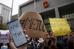 国営中国中央テレビ(CCTV)の人気男性司会者によるセクシュアルハラスメント訴訟が開かれた裁判所の前では支援者らが「#MeToo」などと書かれたプラカードを掲げた=北京で2020年12月2日、AP