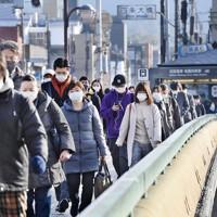 緊急事態宣言の対象地域に追加された京都の四条大橋をマスク姿で歩く人たち=京都市で2021年1月14日午前9時5分、山崎一輝撮影
