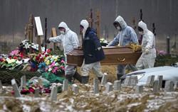 新型コロナの死者をひつぎに入れて運ぶ人々=ロシア西部サンクトペテルブルク近郊で2020年12月15日、AP