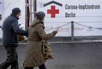Two persons arrive at a new coronavirus, COVID-19, vaccination center in the 'Erika-Hess-Ice-Stadium' in Berlin, Germany, on Jan. 14, 2021. (AP Photo/Michael Sohn)