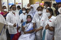 Hospital staff gathers around a health worker, sitting, after she received a COVID-19 vaccine at a government Hospital in Hyderabad, India, on Jan. 16, 2021. (AP Photo/Mahesh Kumar A.)