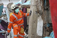 A rescuer inspects the ruin of a building flattened by an earthquake during a search for victims in Mamuju, West Sulawesi, Indonesia, on Jan. 17, 2021. (AP Photo/Joshua Marunduh)