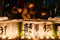 Miumi Shibuya, 24, center, lights a paper lantern with her children in a tribute to victims of the 1995 Great Hanshin Earthquake in Kobe's Chuo Ward, on Jan. 17, 2021. Shibuya was born after the quake, but said she wanted her children to learn about the importance of life. (Mainichi/Kenji Ikai)