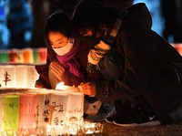 People place their hands together in tribute in front of paper lanterns in a ceremony commemorating victims of the 1995 Great Hanshin Earthquake, at Kobe East Park in Kobe's Chuo Ward on Jan. 17, 2021. (Mainichi/Kenji Konoha)