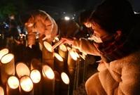 People light bamboo lanterns to commemorate victims of the Great Hanshin Earthquake, at Kobe East Park in Kobe's Chuo Ward on Jan. 17, 2021. (Mainichi/Kenji Ikai)