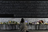 A woman who lost her aunt in the 1995 Great Hanshin Earthquake lays flowers in front of a stone monument bearing the names of victims of the disaster at the Nishinomiya earthquake memorial park in the Hyogo Prefecture city of Nishinomiya on the morning of Jan. 17, 2021. (Mainichi/Tatsuya Fujii)