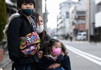 Mika Shigemori, center, talks to her son Soma, left, and daughter Noa, right, in front of the site where her home had been at the time of the 1995 Great Hanshin Earthquake, in Kobe's Hyogo Ward, on Jan. 17, 2021. (Mainichi/Naohiro Yamada)