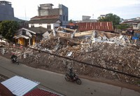 Motorists ride past buildings collapsed in Friday's earthquake in Mamuju, West Sulawesi, Indonesia, on Jan. 18, 2021. (AP Photo/Yusuf Wahil)