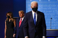 In this Oct. 22, 2020, file photo first lady Melania Trump, left, and President Donald Trump, center, remain on stage as Democratic presidential candidate former Vice President Joe Biden, right, walk away at the conclusion of the second and final presidential debate at Belmont University in Nashville, Tenn. (AP Photo/Julio Cortez)