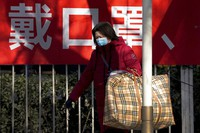 A woman wearing a face mask to help curb the spread of the coronavirus walks by a banner baring the words