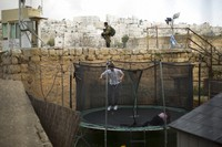 In this March 7, 2019, file photo, settlers jump on a trampoline as an Israeli solider stands guard in the Israeli controlled part of the West Bank city of Hebron. (AP Photo/Ariel Schalit)