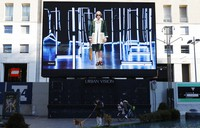 People stand at the bottom of a giant screen streaming a Fendi fashion live show during the Milan's fashion week in Milan, Italy, on Jan. 15, 2021. (AP Photo/Antonio Calanni)