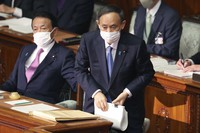 Japanese Prime Minister Yoshihide Suga, right, attends an ordinary Diet session at the upper house of parliament in Tokyo, on Jan. 18, 2021. (AP Photo/Koji Sasahara)