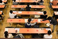 Examinees are seen receiving answer sheets ahead of the first ever administration of the new standardized college exams, at the University of Tokyo in Bunkyo Ward, Tokyo, on Jan. 16, 2021. Seats that cannot be used as part of coronavirus prevention measures to maintain distance between individuals are seen marked out with red x symbols. (Mainichi/Kaho Kitayama)
