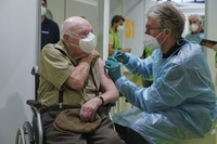 A doctor inoculates Herri Rehfeld, 92, against the new coronavirus with the Pfizer/BioNTech vaccine at the vaccination center at the Messe Berlin trade fair grounds on the center's opening day in Berlin, Germany, on Jan. 18, 2021. (Sean Gallup/Getty Images via AP, Pool)