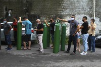 Family members of patients hospitalized with COVID-19 line up with empty oxygen tanks in an attempt to refill them, outside the Nitron da Amazonia company, in Manaus, Amazonas state, Brazil, on Jan. 15, 2021. (AP Photo/Edmar Barros)
