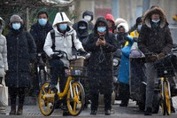 Commuters wearing face masks to protect against the spread of the coronavirus wait at an intersection during a snowy morning in Beijing, on Jan. 19, 2021. (AP Photo/Mark Schiefelbein)