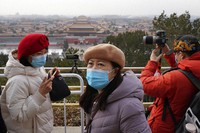 Visitors wear masks as they enjoy the view overlooking the Forbidden City from Jingshan park during a snow day in Beijing on Jan. 19, 2021. (AP Photo/Ng Han Guan)