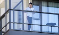 Serbia's Novak Djokovic stands on the balcony at his accommodation in Adelaide, Australia, on Jan. 19, 2021. (Morgan Sette/AAP Image via AP)