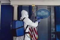 In this Oct. 5, 2020 file photo, a member of the cleaning staff sprays the James Brady Briefing Room of the White House on Oct. 5, 2020, in Washington. (AP Photo/Alex Brandon, File)