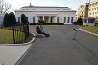 A cameraman waits by an unused microphone stand outside the West Wing at the White House on Jan. 19, 2021, in Washington. (AP Photo/Gerald Herbert)
