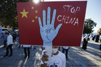 In this file photo taken Thursday, Oct. 1, 2020, a protester from the Uighur community living in Turkey, holds an anti-China placard during a protest in Istanbul, , against what they allege is oppression by the Chinese government to Muslim Uighurs in far-western Xinjiang province. (AP Photo/Emrah Gurel, File)