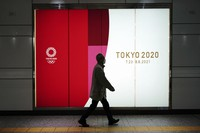 A man wearing a protective mask walks near a banner for the Tokyo 2020 Olympics at an underpass in Tokyo on Jan. 19, 2021. (AP Photo/Eugene Hoshiko)