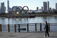 A man wearing a protective mask to help curb the spread of the coronavirus walks near the Olympic rings floating in the water in the Odaiba section in Tokyo, on Jan. 20, 2021. (AP Photo/Eugene Hoshiko)