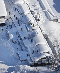 The roof of an elementary school building in the city of Yokote, Akita Prefecture, is seen being cleared of snow by members of the Japan Ground Self-Defense Force (GSDF) on Jan. 6, 2021 in this image taken by a Mainichi Shimbun helicopter. Due to the heavy snowfall, it's become difficult for individuals to remove snow on their own, and the GSDF have been called in to numerous areas. (Mainichi)