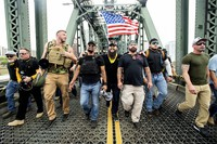 Members of the Proud Boys, including organizer Joe Biggs, third from right, march across the Hawthorne Bridge during an