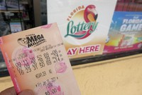 In this Jan. 13, 2021 file photo, a customer shows off a Mega Millions lottery ticket after purchasing it, in Orlando, Florida. (AP Photo/John Raoux)