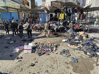 People and security forces gather at the site of a deadly bomb attack in a market selling used clothes, in Iraq, on Jan. 21, 2021. (AP Photo/Hadi Mizban)