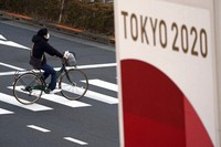 A man wearing a protective mask to help curb the spread of the coronavirus rides a bicycle near a banner of the Tokyo 2020 Olympics in Tokyo, on Jan. 21, 2021. (AP Photo/Eugene Hoshiko)