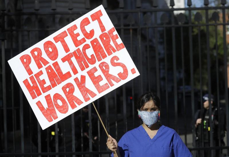 「医療従事者を守れ」と書かれたプラカードを掲げて首相官邸前で抗議するミーナル・ビズさん=ロンドンで2020年4月19日、AP