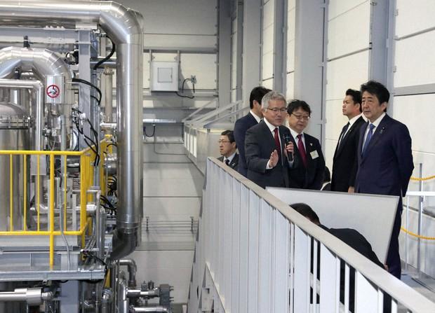 福島水素エネルギー研究フィールドを訪れ、水素製造設備を視察する安倍晋三首相(右、当時)=福島県浪江町で2020年(令和2年)3月7日、代表撮影