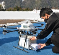 A town official puts goods in a box attached beneath a drone in Misato, Shimane Prefecture, on Jan. 14, 2021. (Mainichi/Kenichi Kayahara)
