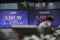 A currency trader walks by the screens showing the Korea Composite Stock Price Index (KOSPI), left, and the foreign exchange rate between U.S. dollar and South Korean won at the foreign exchange dealing room in Seoul, South Korea, on Jan. 22, 2021. (AP Photo/Lee Jin-man)