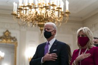 President Joe Biden, accompanied by first lady Jill Biden, places his hand over his heart during a performance of the national anthem, during a virtual Presidential Inaugural Prayer Service in the State Dinning Room of the White House, on Jan. 21, 2021, in Washington. (AP Photo/Alex Brandon)