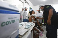 A woman of the Ticuna Indigenous group gets her shot of the COVID-19 vaccine produced by China's Sinovac Biotech Ltd, during the start of the vaccination plan on indigenous lands at the Ticuna de Umariacu village health post in Tabatinga, Amazonas state, Brazil, on Jan. 19, 2021. (AP Photo/Andre Borges)