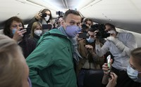 In this Jan. 17, 2021 file photo, Alexei Navalny is surrounded by journalists inside the plane prior to his flight to Moscow at the Berlin Brandenburg Airport in Schoenefeld, near Berlin, Germany. (AP Photo/Mstyslav Chernov)