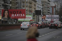 Cars drive past election campaign billboards for presidential candidates Marisa Matias, left, and Andre Ventura, right, in Lisbon, Portugal, on Jan. 19, 2021. (AP Photo/Armando Franca)