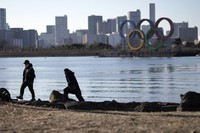 A man and a woman walk near the Olympic rings floating in the water in the Odaiba area in Tokyo on Jan. 20, 2021. (AP Photo/Eugene Hoshiko)