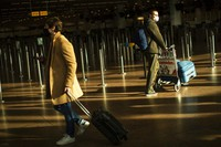 Travellers, wearing face masks to prevent the spread of the coronavirus COVID-19, walk along the departure hall of the Zaventem international airport in Brussels, on Jan. 22, 2021. (AP Photo/Francisco Seco)